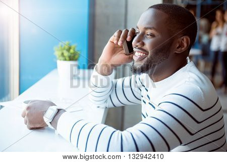Modern way of communication. Happy and cheerful modern young man talking on a smartphone and being in a good mood