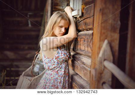 romantic sad girl near rustic wooden wall