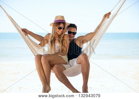 Couple Having Fun In A Hammock At The Beach