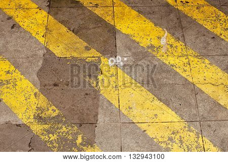 Yellow striped road markings on cement squares