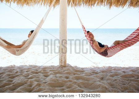 Young Couple Sleeping In Hammocks At The Beach