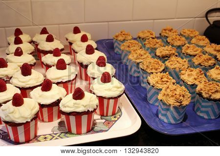 red raspberry and peanut brittle birthday cupcakes on trays