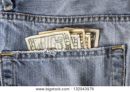 A back pocket of blue jeans showing american money fanned out.