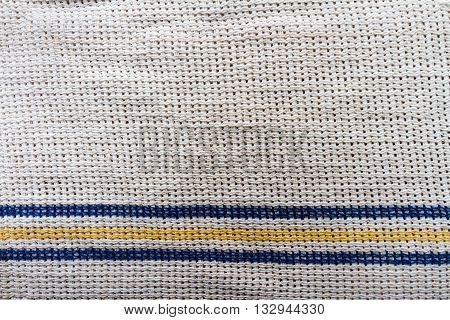 White cloth fabric with blue and yellow stripes