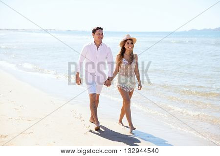 Couple Of Newlyweds Walking Down The Beach
