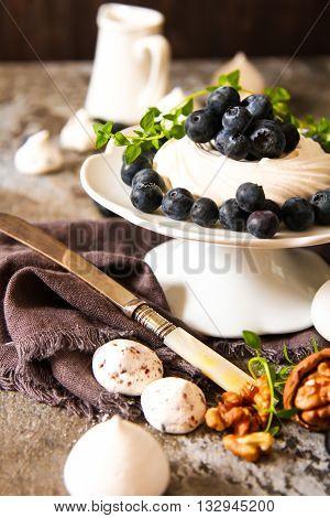 Meringue Pavlova Cake With Fresh Blueberries And Walnuts On Dark
