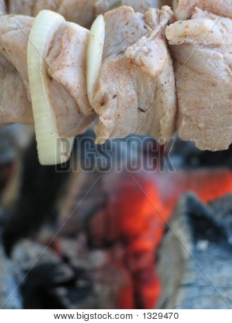 La carne a las brasas calientes del fondo.