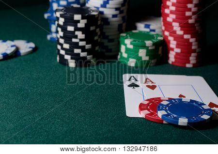 Stack of casino chips and two aces on the green table. Poker game backdrop