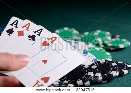 Stack of chips and four of kind poker combination on a green background. Poker game theme