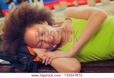Closeup of beautiful female backpacker tourist napping on a bench and baggage at the station