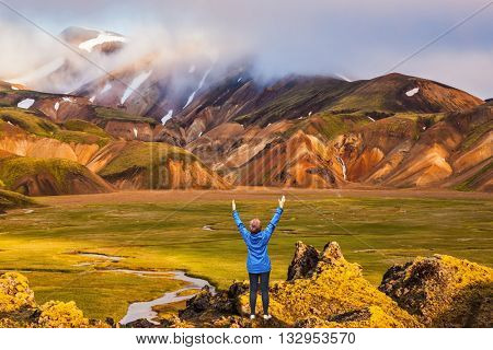 Great Valley Park Landmannalaugar, surrounded by mountains of rhyolite and unmelted snow. Iceland in July. Elderly lady shocked landscape