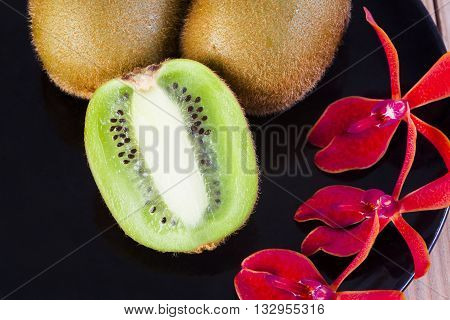 Kiwi fruit  is placed on the container ornamental orchids.