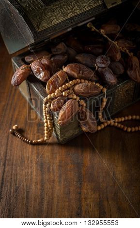 Fine quality Arabian dates stored in antique wooden trunk with Islamic prayer beads. Ramadan food and objects.