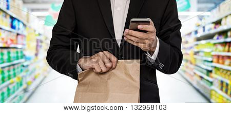 Businessman holding brown paper bag, while using smart phone at mall