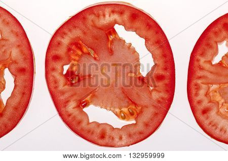 Close up of tomato slice. A close up image of sliced tomatoes layed out on a white background.