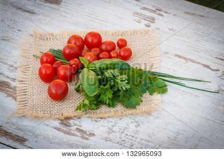 Red Cherry Tomatoes With Green Parsley And Basil On Jute Canvas In Garden On Sunny Day
