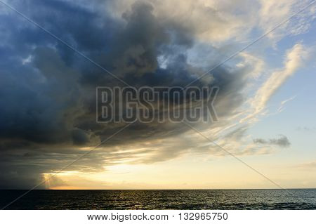 Storm clouds is an ominous storm moving in over the ocean as a bright set of sunrays burst through the darkness to light the way.