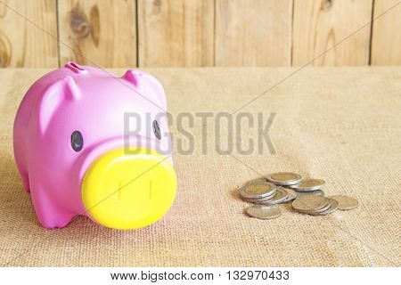 Pink piggy bank and coins background is wood.