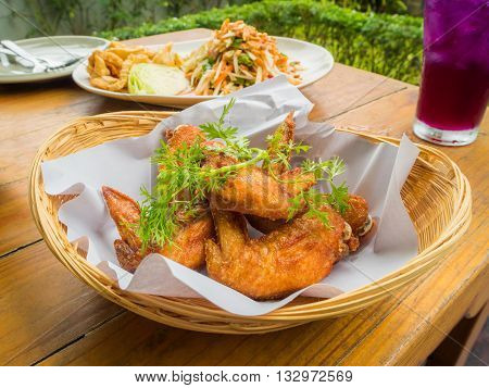 Thai food culture. Chicken fried in basket papaya salad and ice crake lemon tea on wooden table in garden of restaurant Selective Focus