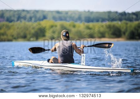 Chelyabinsk, Russia - May 28, 2016: athlete rower on rowing kayak on lake, splashes of water under paddle during Ural championship in rowing