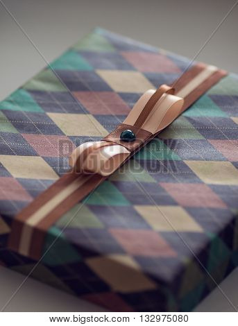 Photo of Vintage Christmass Gift Box. Closeup of Wrapped Xmas Gift Box with Tiny Gold Ribbon Bow