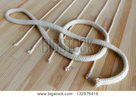 Treble clef and stave made with white ropes on the deck