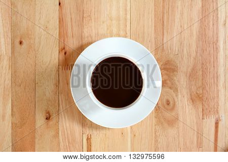 Coffee cup with black coffee on wood table, top view