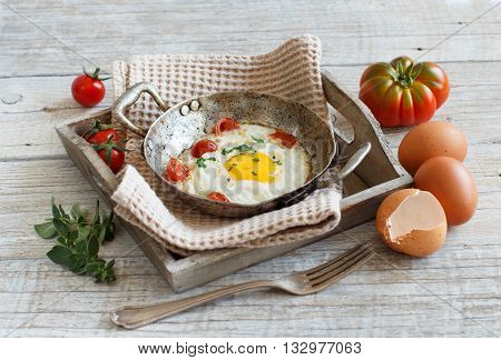 Fried egg with tomatoes and herbs on a old frying pan on wood