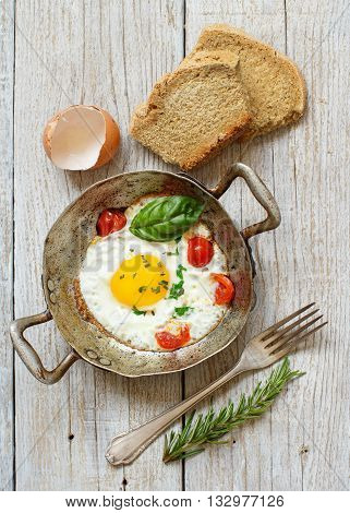 Fried egg with tomatoes homemade bread and herbs on a old frying pan on wood