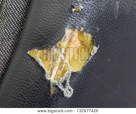 Torn leather at the back view of old black revolving office chair selective focus
