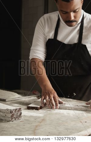 Unfocused Black Man Chief Cooks Chocolate Cakes In Sugar Powder For Sale In His Professional Artisan