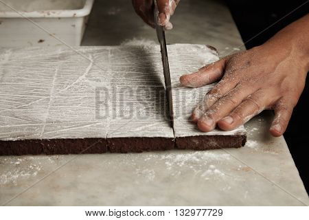 Close Up Black Man Hands Cut Slice Of Freshly Baked Chocolate Cake On Marble Table In Professional A