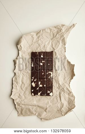 Freshly Baked Organic Healthy Chocolate Bar With Nuts And Oats On Craft Paper, Isolated On White Tab