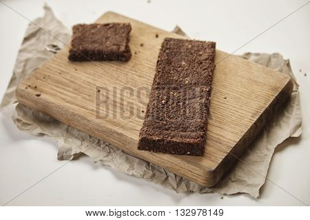 Artisan Organic Freshly Baked Healthy Chocolate Bar With Berries And Grinded Nuts On Wooden Board An