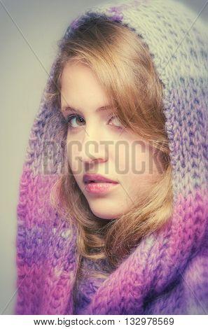 Studio portrait of a pretty blond teenager girl wearing a wool scarf in her head