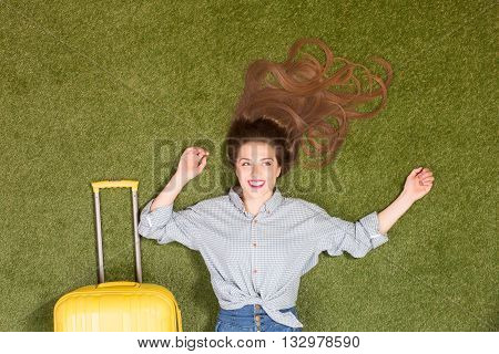 Portrait of beautiful tourist lady lying on green grass. Pretty lady with long brown hair lying near yellow luggage. Ready for travelling, trip or journey.