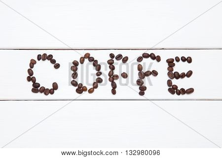 Coffee beans arranged in the word coffe on white wooden