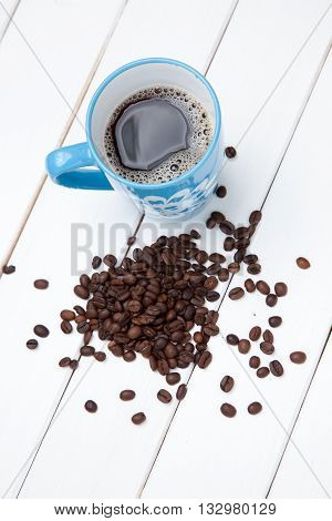 Close-up Of A Cup Of Coffee  And Beans On White Wooden Table