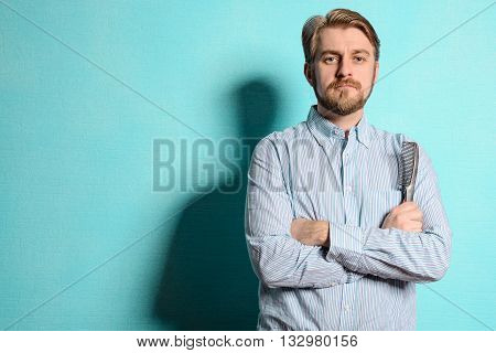 Portrait Of Young Hairstylist Standing Against Blue Background