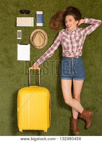 Happy smiling beautiful tourist lady lying on green grass and holding yellow luggage. Pretty woman looking at camera white mobile or smart phone, passport, map or guide, etc. represented near her.