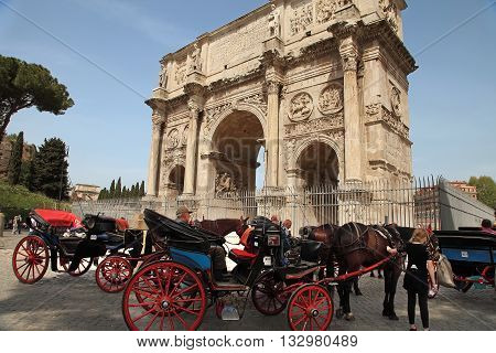 ROMA ITALY APRIL 7 2016 : Coachman sits on a carriage pulled by a horse waiting for tourists. Arco de Constantino (Arch of Constantine) and Colosseum. The arch was erected by the Roman Senate to commemorate Constantine victory over Maxentius