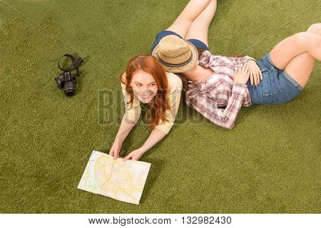 Portrait of beautiful tourist ladies lying on green grass, resting and relaxing with nature. Pretty lady with red hair lying in front of map or guide. Tourism concept.