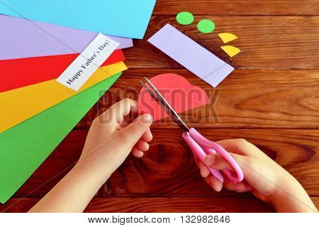 Child keeps scissors in hands and cuts a car of paper. Colored paper sheets, scissors, cut-out detail. Child makes a gift for dad. Home made fathers day gift idea. Wooden background. Kids workplace
