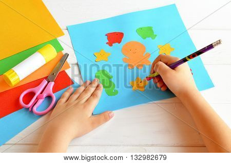 Child keeps a pencil in hand and draws. Scissors, glue stick, colorful paper, children applique. Cute paper sea animals. Kids skills. Crafts project idea. Kindergarten paper and glue crafts activity