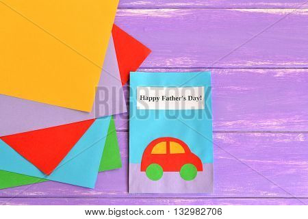 Greeting card with with paper car and text Happy father's day, pieces of colored paper on a light purple wooden background. Crafts card from colored paper. Gift idea for dad. Fathers day background.