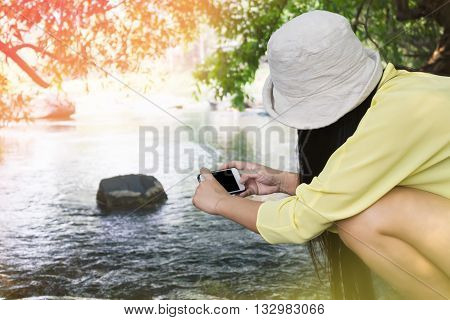 Women back or rare view sitting shooting photo via smartphone or mobile at stream or river in cheerful summer day relaxing women with smartphone and lifestyle with nature