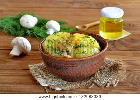 Stewed potatoes with mushrooms, spices, dill and vegetable oil. Green dill, fresh mushrooms, sunflower oil, spoon on wooden table. Slow-cooked potatoes with mushrooms. Cheap and healthy lunch, dinner