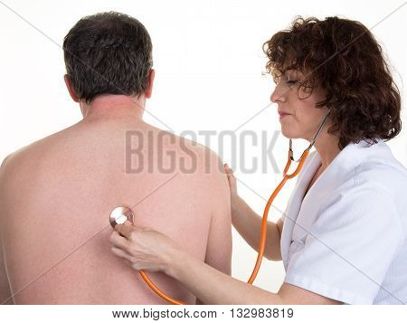Woman Doctor Listening To Man's Heartbeat In Hospital
