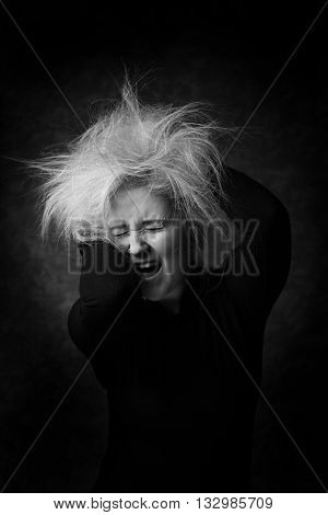 Sexy young woman putting hands in her disheveled hair. Sexy look in black and white portrait. Screaming woman with messy hair.