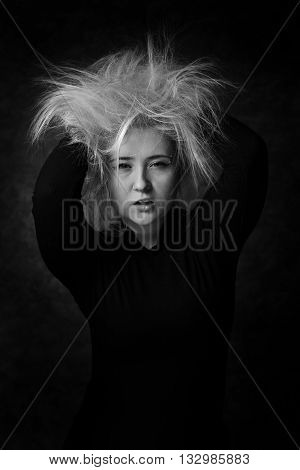 Portrait of a woman in black and white that putting hands in her disheveled hair.